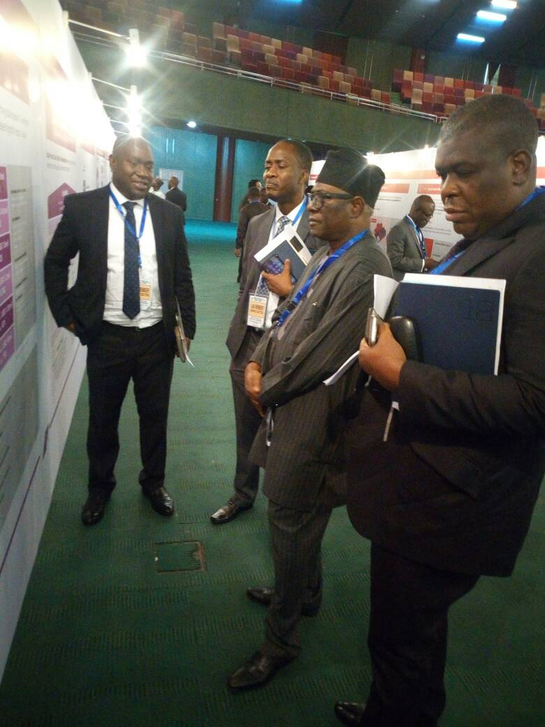 Dr. Toni Ogunbor and the Nosak Group Team at the ERGP event observing a designed banner on a wall